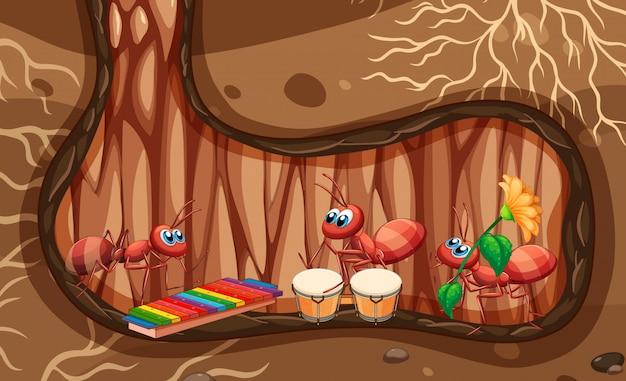 Scena sotterranea con le formiche che suonano musica nel buco