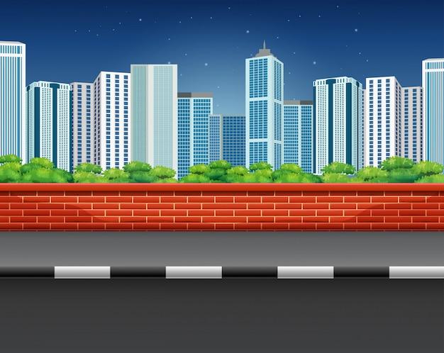 Scenario di una strada con recinzione in mattoni e paesaggio urbano
