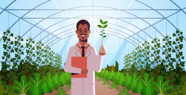 Scienziato che esamina campione della pianta nella ricerca interna moderna della serra di vetro della provetta