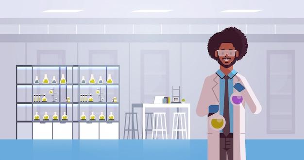 Scienziato in possesso di provette con liquidi colorati