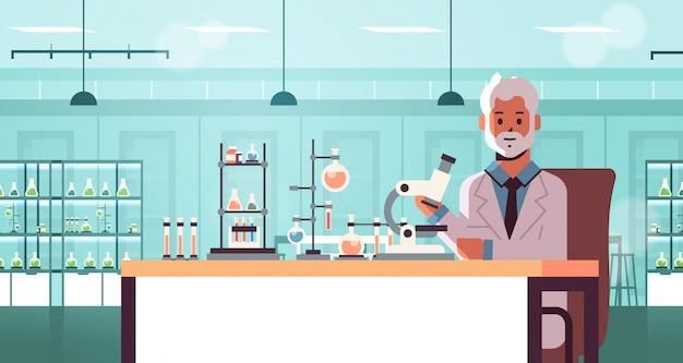Scienziato senior che per mezzo del microscopio e provi il ritratto orizzontale di concetto di tubesscience