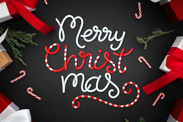 Scritte in merry christmas con regali e bastoncini di zucchero