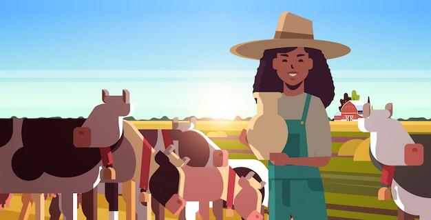 Secchio della holding del milkwoman con il coltivatore femminile del latte fresco che sta vicino al gregge delle mucche che pascono sul campo erboso