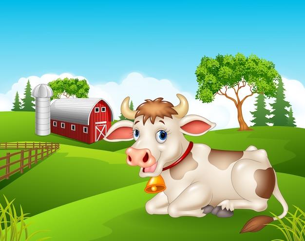 Seduta felice della mucca isolata nell'azienda agricola