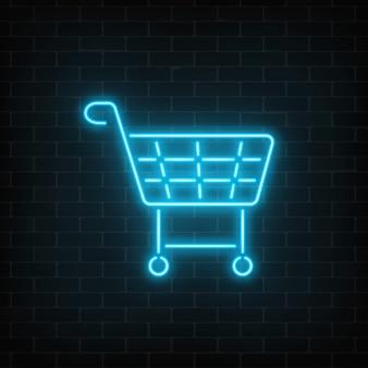 Segno al neon d'ardore del carrello del supermercato su un fondo scuro del muro di mattoni. cestino per negozio di effetti di luce.