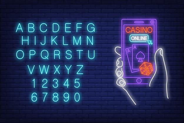 Segno al neon online del casinò. alfabeto inglese e numeri. mano che tiene smartphone con i dadi