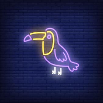 Segno al neon tucano. uccello tropicale sul fondo scuro del muro di mattoni. pubblicità luminosa di notte