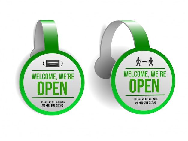 Segno aperto sull'etichetta verde - bentornato. set di informazioni segno di fronte alla porta di lavorare di nuovo. mantieni la distanza sociale e indossa la maschera. isolato su bianco