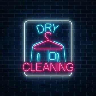 Segno d'ardore delle lavanderie a secco al neon con il gancio e la camicia su un muro di mattoni scuro