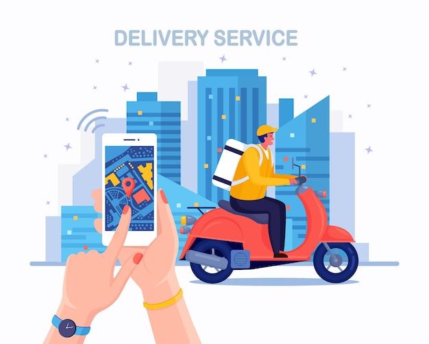 Servizio di consegna veloce gratuito in scooter. il corriere consegna l'ordine del cibo. tenere in mano il telefono con l'app mobile. monitoraggio del pacco online. l'uomo viaggia con un pacco in giro per la città. spedizione espressa. design