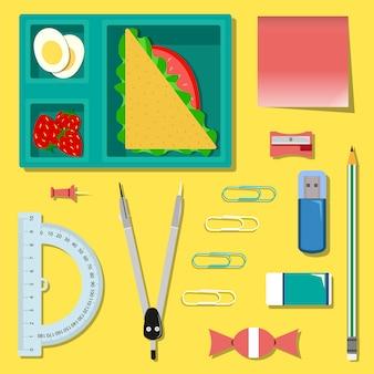 Set di articoli di cancelleria con pranzo al sacco sul tavolo. set scuola o ufficio.