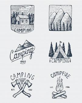 Set di incisi vintage, disegnati a mano, vecchi, etichette o badge per campeggio, trekking, caccia con picchi di montagna, casa, ascia e tenda, falò con foresta