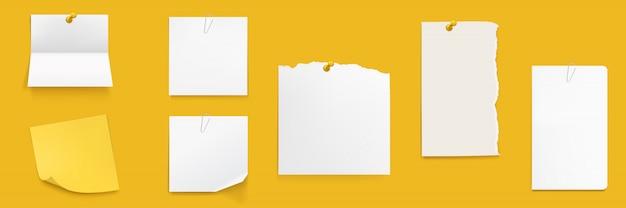 Set di note di carta, fogli di quaderno bianco sul muro