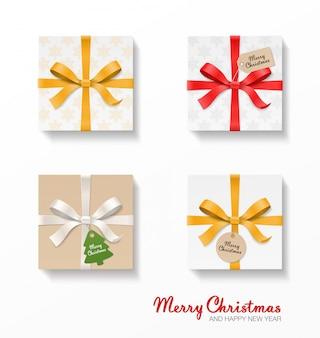 Set regalo quadrato. nodo di fiocco color oro, rosso, argento, nastri, pallina kraft e cartellini pendenti. motivo a fiocchi di neve, vecchia carta. testo di buon natale.