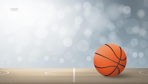 Sfera di pallacanestro su campo in legno.