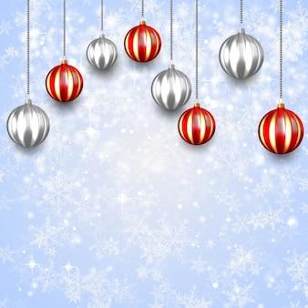 Sfere rosse e d'argento di natale su sfondi di fiocchi di neve