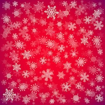Sfondo di natale rosso con diversi fiocchi di neve