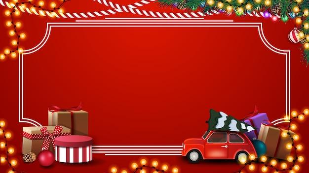 Sfondo di natale rosso con regali, cornice d'epoca, ghirlanda, rami e albero di natale rosso che trasportano auto d'epoca