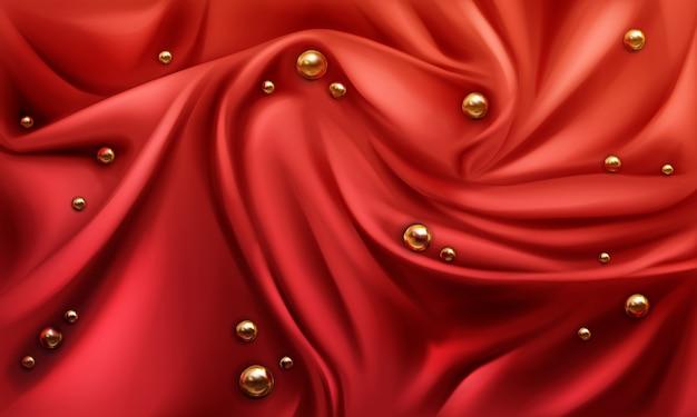 Sfondo di stoffa drappeggiata di seta rossa con sfere lucenti o perle d'oro sparse a caso.