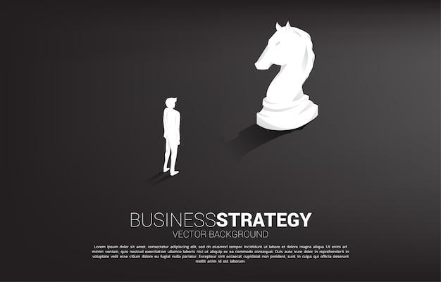 Sfondo di strategia aziendale con pezzo degli scacchi uomo d'affari e cavaliere