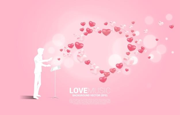 Silhouette del direttore d'orchestra in piedi con il tasto del pianoforte con palloncino cuore che vola. priorità bassa di concetto per la canzone d'amore e il tema del concerto.