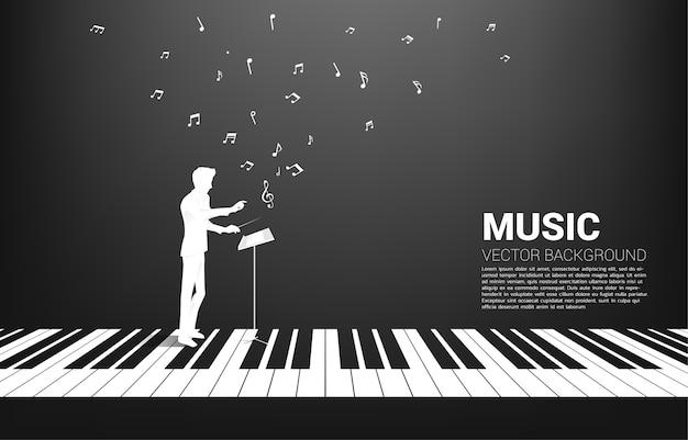 Silhouette del direttore d'orchestra in piedi con il tasto del pianoforte con una nota musicale volante. priorità bassa di concetto per il concerto di pianoforte e la ricreazione.