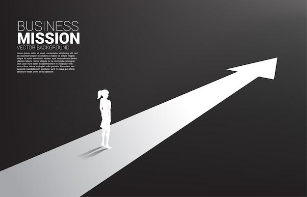Silhouette di imprenditrice in piedi su una freccia in avanti