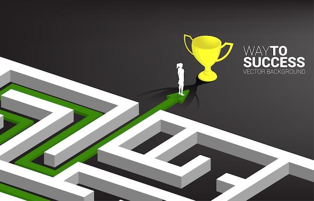 Silhouette di imprenditrice sulla freccia con percorso percorso per uscire dal labirinto al trofeo d'oro. concetto di business per problem solving e strategia di soluzione
