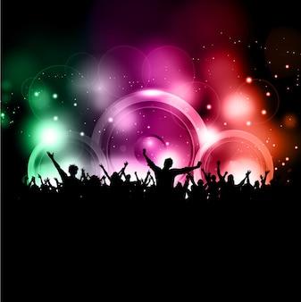 Silhouette di una folla di partito su uno sfondo di luci incandescenti