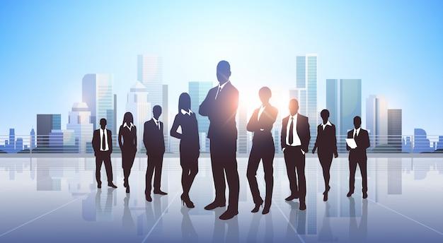 Silhouette di uomini d'affari in piedi sopra la città moderna
