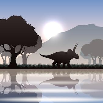 Siluetta del dinosauro del triceratopo in paesaggio scenico con la montagna del lago e gli alberi giganti