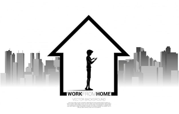 Siluetta del telefono cellulare di uso dell'uomo nella casa con il fondo della città. concetto per il lavoro a distanza da casa e tecnologia.