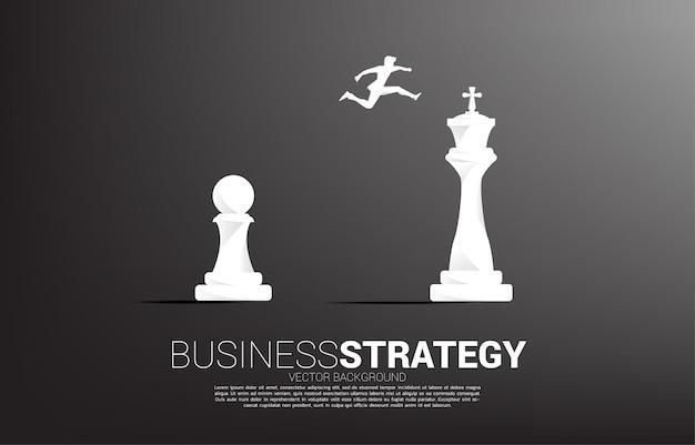 Siluetta dell'uomo d'affari che salta sul pezzo degli scacchi dal pegno al re. concetto di obiettivo, missione e strategia aziendale