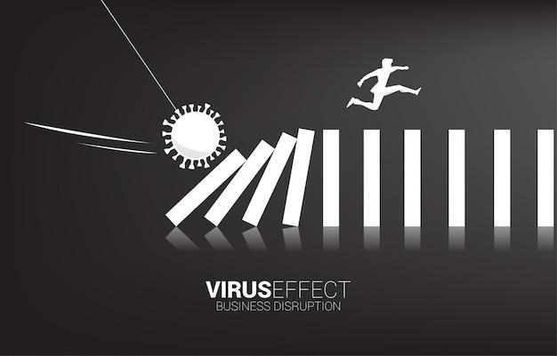 Siluetta dell'uomo d'affari che salta via sul domino di crollo dall'effetto del virus della corona. concetto di business di interruzione dell'attività ed effetto domino dalla pandemia.