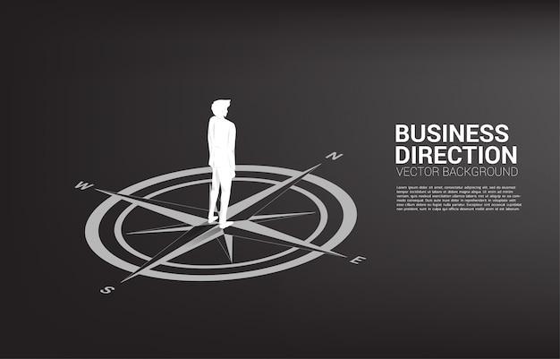 Siluetta dell'uomo d'affari che sta al centro della bussola sul pavimento. percorso di carriera e direzione aziendale