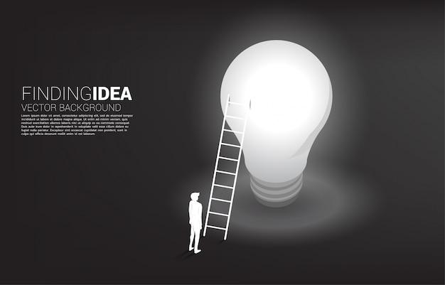 Siluetta dell'uomo d'affari che sta con la scala sulla lampadina.