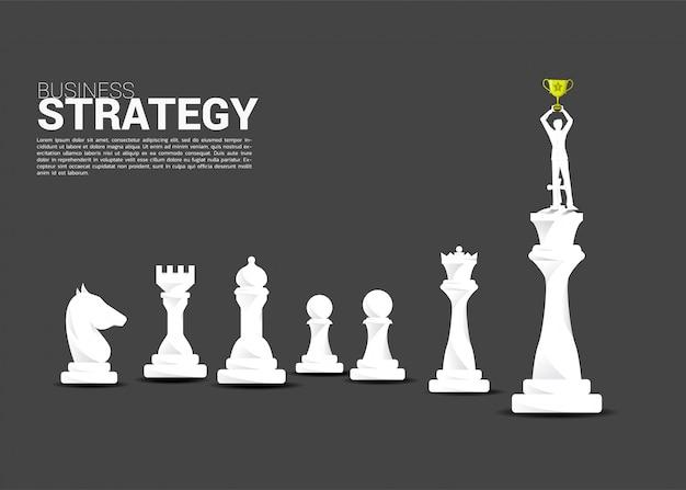 Siluetta dell'uomo d'affari che sta sul pezzo degli scacchi di re