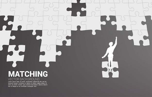 Siluetta dell'uomo d'affari che sta sul pezzo finale del puzzle.