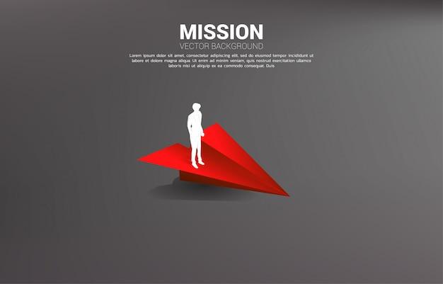 Siluetta dell'uomo d'affari che sta sull'aeroplano di carta rosso di origami. business concetto di leadership, avviare business e imprenditore
