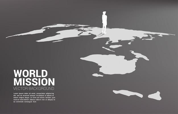 Siluetta dell'uomo d'affari che sta sulla mappa di mondo.