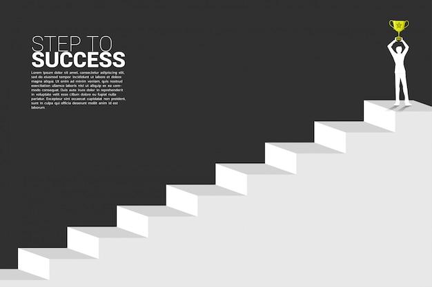 Siluetta dell'uomo d'affari con il trofeo del campione sopra la scala. concetto di business in crescita, successo nel percorso di carriera.