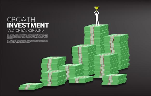 Siluetta dell'uomo d'affari con il trofeo del vincitore che si leva in piedi in cima al grafico di sviluppo con la pila di banconota.