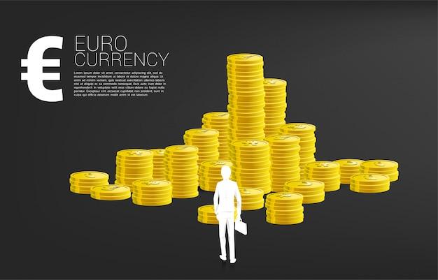 Siluetta dell'uomo d'affari con la cartella che si leva in piedi davanti all'euro soldi e pila di moneta. concetto di business di successo ed economia della zona euro.