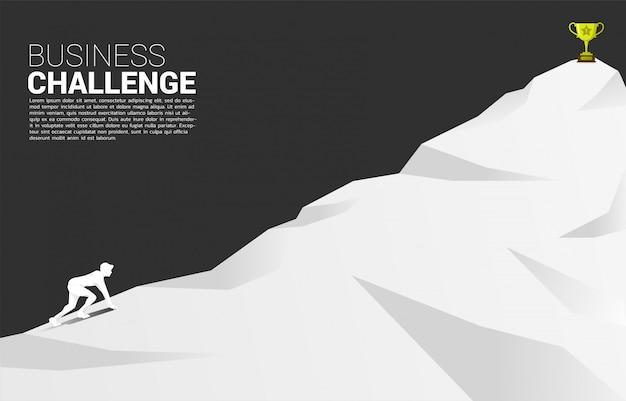 Siluetta dell'uomo d'affari pronta a correre al trofeo in cima alla montagna.