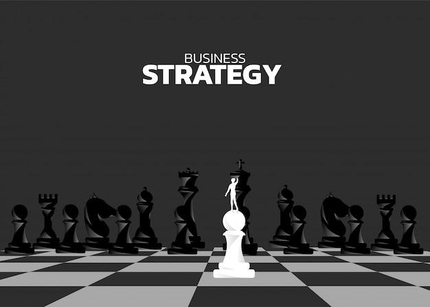 Siluetta dell'uomo d'affari sul pegno che sta davanti al pezzo degli scacchi