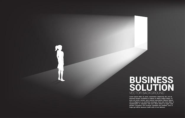 Siluetta della donna di affari che sta davanti al fondo della porta di uscita