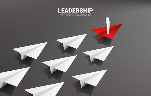 Siluetta della donna di affari che sta sul gruppo principale dell'aeroplano di carta rosso di origami di bianco. concetto di business di missione di leadership e visione.