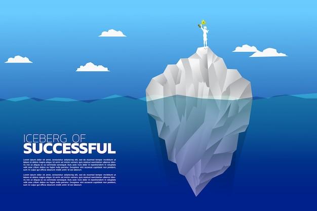 Siluetta della donna di affari con il trofeo del campione in cima all'iceberg.