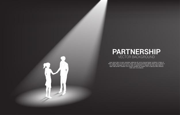 Siluetta della stretta di mano della donna di affari e dell'uomo d'affari in riflettore. concetto di collaborazione e collaborazione del lavoro di gruppo.