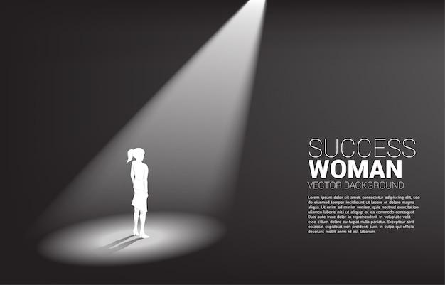 Siluetta delle donne di affari che stanno nel fondo del riflettore